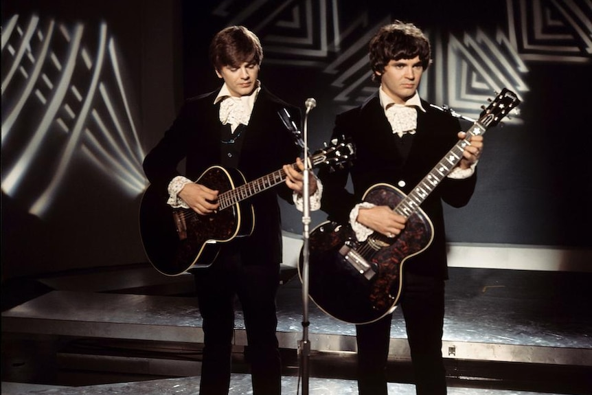 Two 1960s guitarists stand on stage in dark suits in front of black and white background.