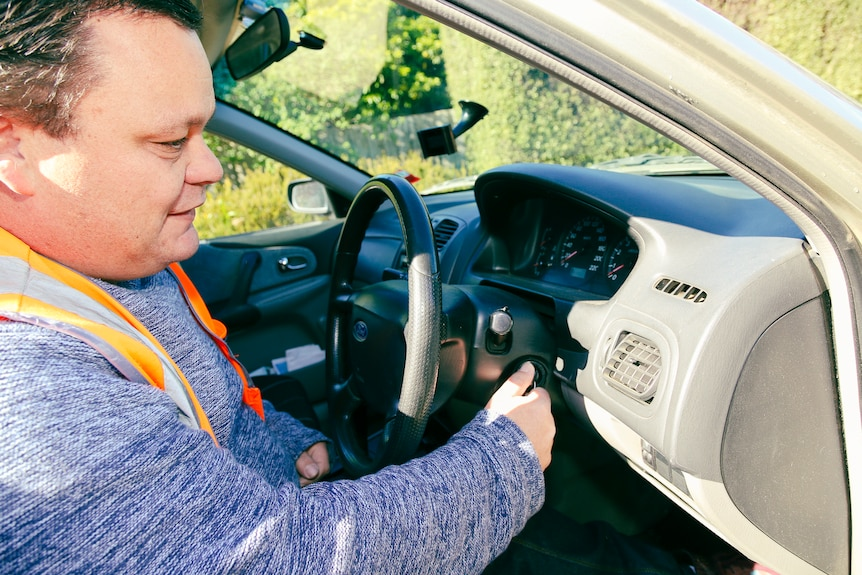 A man in a high-vis vest turns the key in the ignition of his car.
