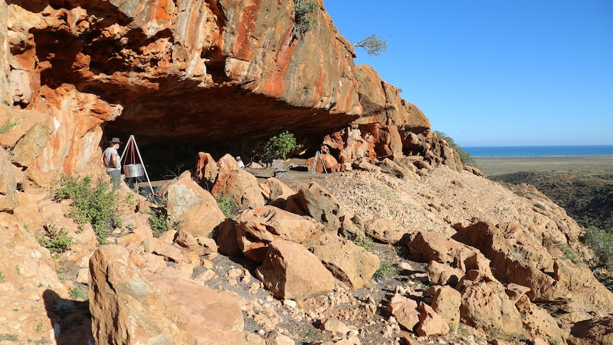 A red rock cave with research equipment in it. In the background there is a blue ocean and sky