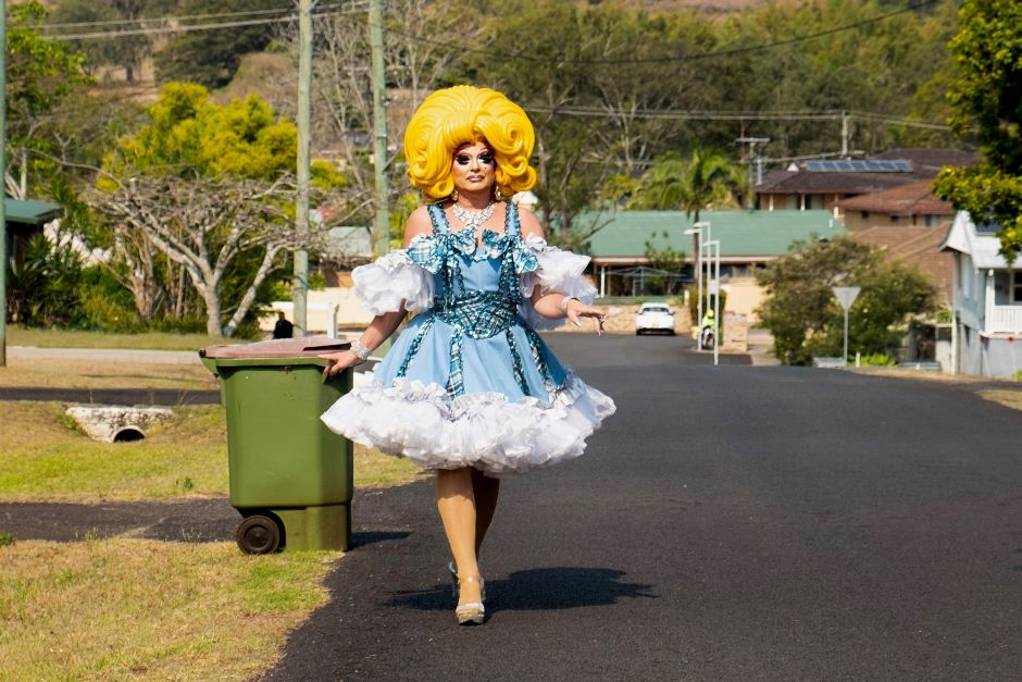 Drag queen in bright yellow wig and blue dress with wheelie bin