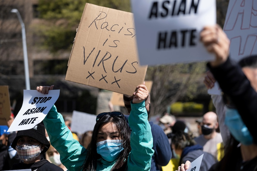 A young Asian woman in a face masks holds up different signs with her hands in daytime rally.