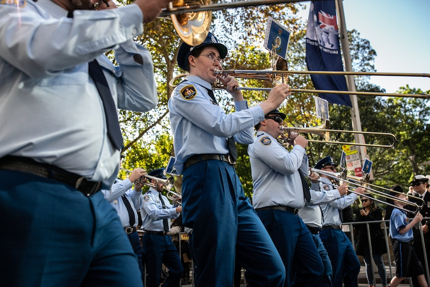 A woman in uniform marches in a line while playing the trombone.