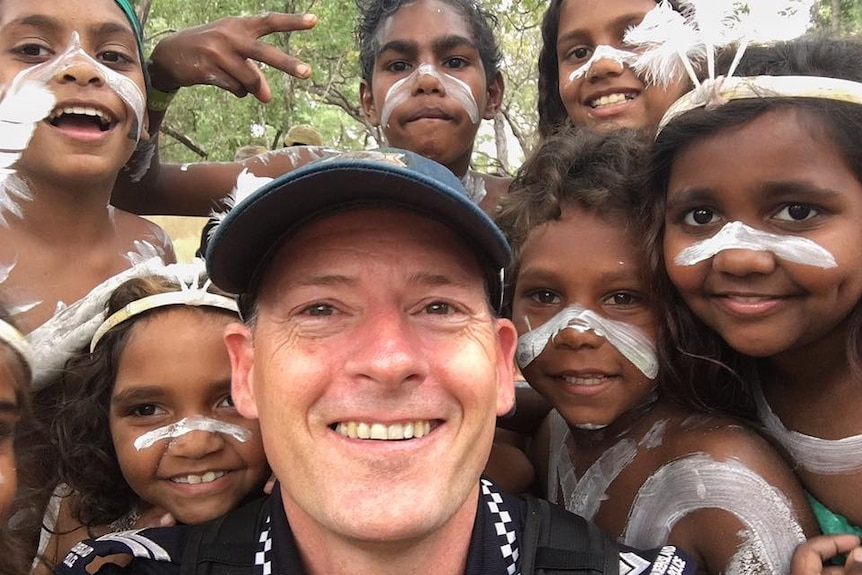 Selfie of police officer surrounded by young Aboriginal dancers in costume.