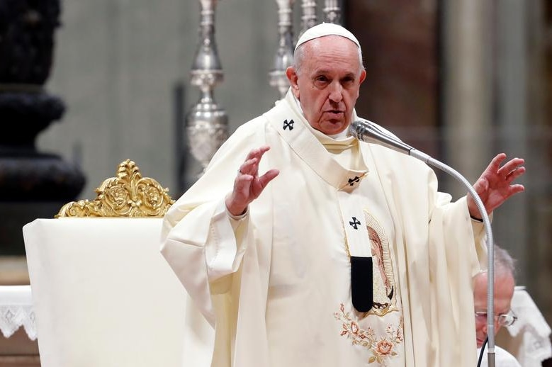 Pope Francis speaking into a microphone.