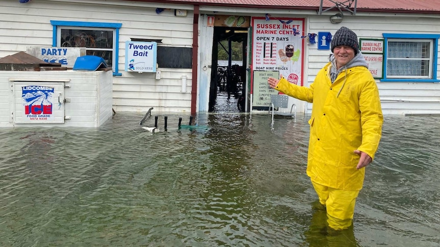 A man stands outside a flooded shopfront.