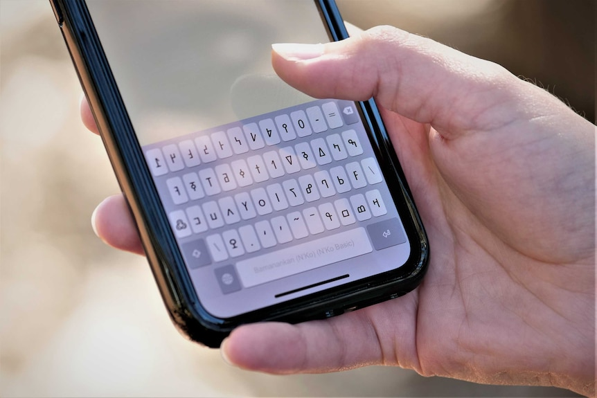 A close up of a phone keyboard in a language other than English.