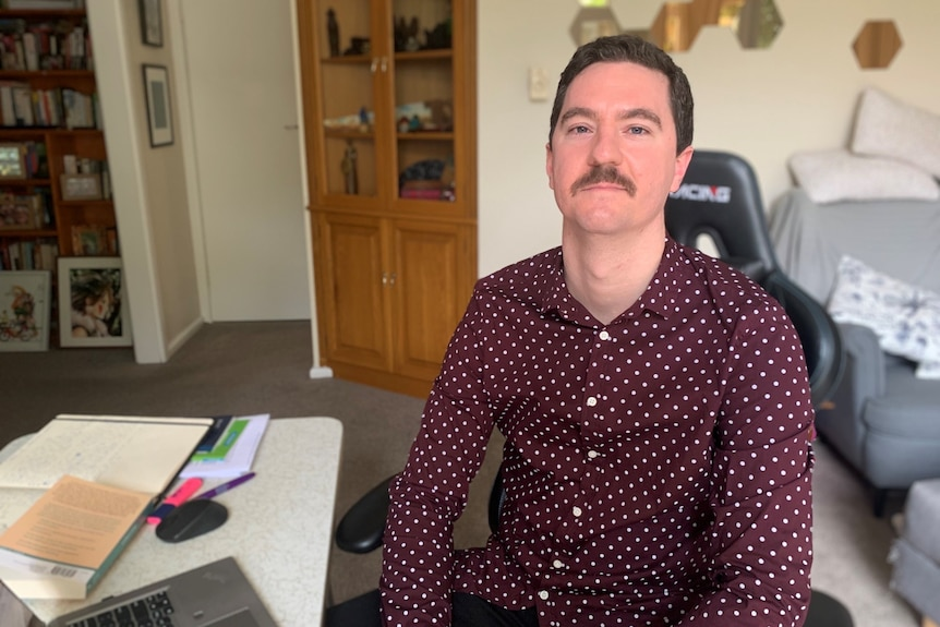 A young moustached man wearing polka dot burgundy shirt sits in front of laptop, looks at the camera.