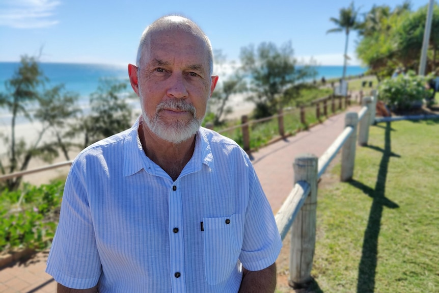 Chris Mitchell standing in footpath in front of beach