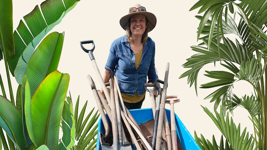 Gardening Australia presenter Millie Ross holds a wheelbarrow filled with garden tools like shovels, to make gardening easier.