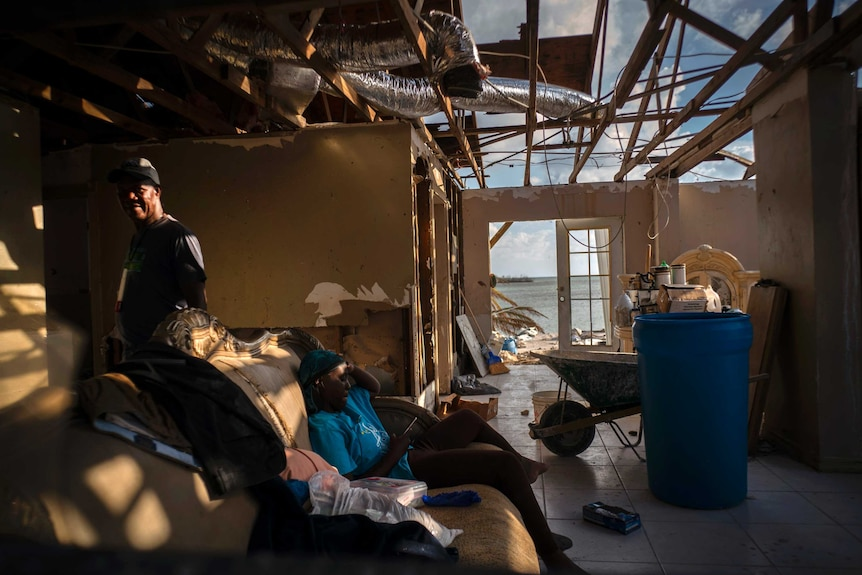 A man stands to the left while his daughter sits on a couch. Half the roof is missing off their home.
