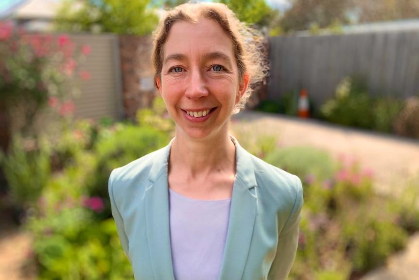 a woman in a blazer, smiling in a garden