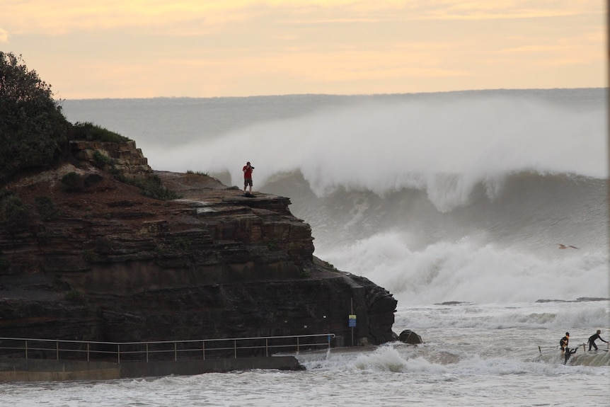 A man stands on the rocks photographing the swell at Narrabeen North beach.