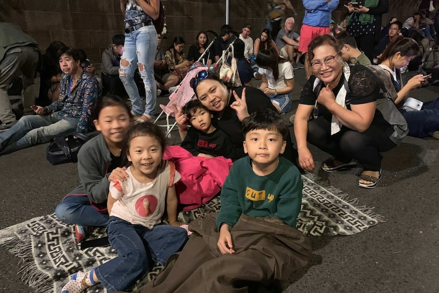 A crowd of people sit on the crowd and one family smiles for a photo