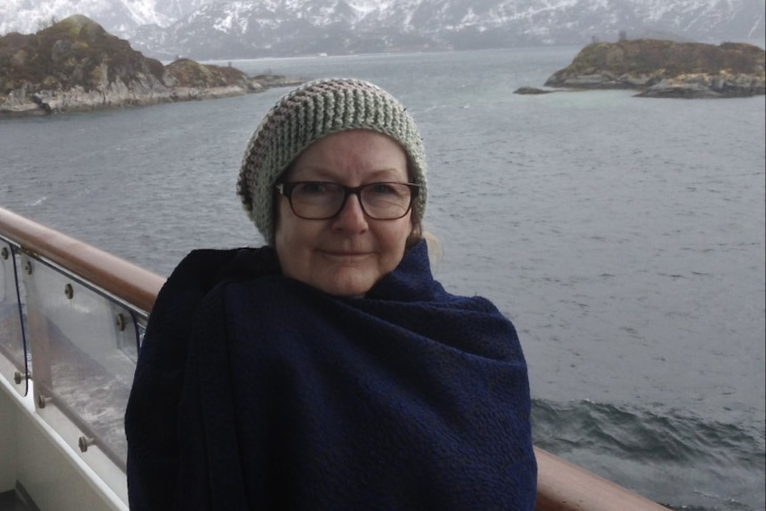 A woman in a beanie poses for a photo on a boat