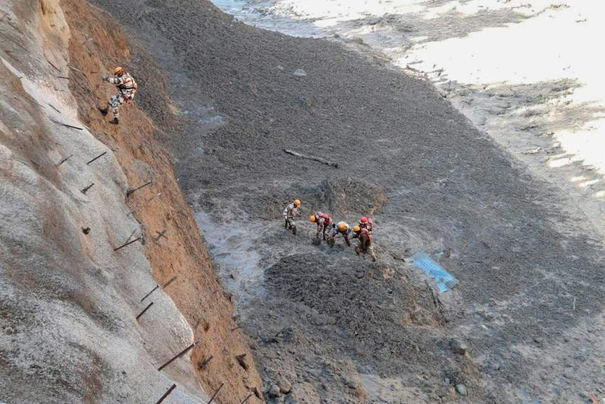 Five rescue personnel dig through mud and rock in an area smashed by surging water, while another rescuer abseils down to them.