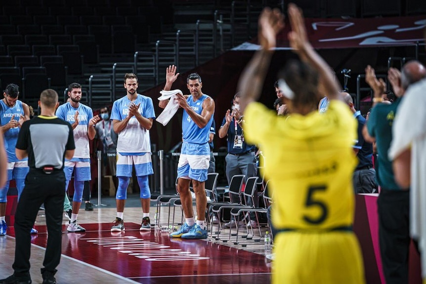 Luis Scola stands on a basketball court with his hand in the air as others stand and clap