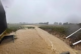 A picture of flood water flowing across a field, next to a building.
