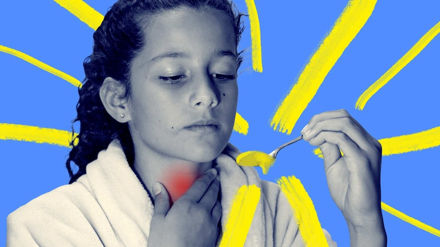 Child with red throat about to take a spoonful of honey which may help with her cough.