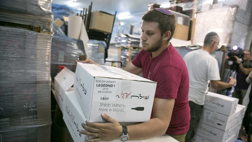 A worker carries boxes containing wine bottles for export at Shiloh Wineries.