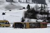 A train carriage lies on its side in the snow.
