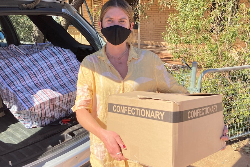 Sarah Donnelley holding care packages for Wilcannia residents