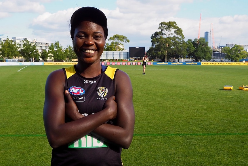 A woman dressed in a AFLW uniform stands with arms crossed and smiling looking at the camera on a football oval.
