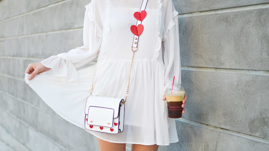 Woman in a white dress holds a coffee showing how vintage clothes can refresh your wardrobe for cheap.