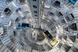 SUV vehicles are seen from the center of a high delivery tower.