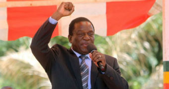 Emmerson Mnangagwa holds one arm up in the air as he speaks into a microphone.