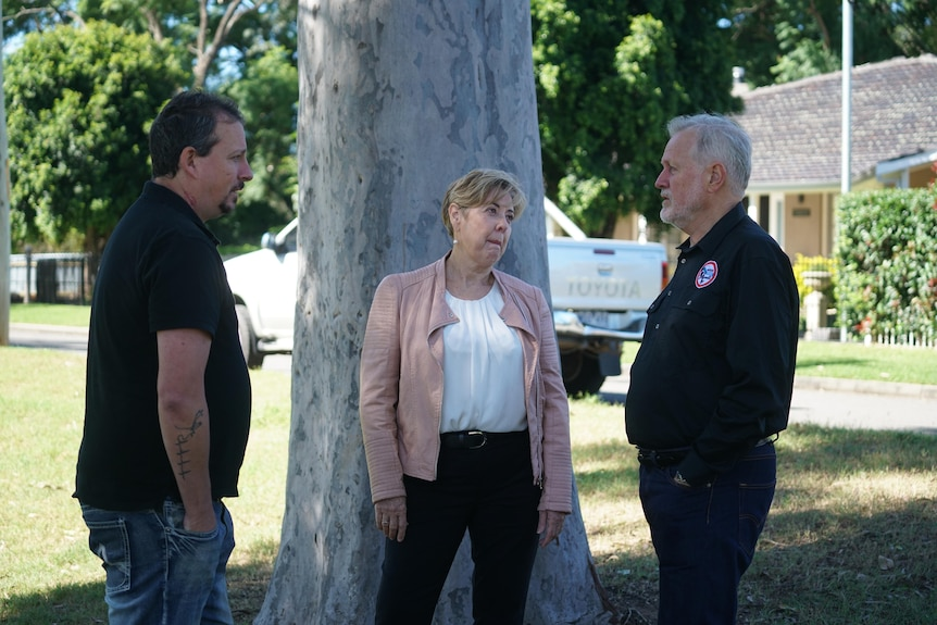 Two men in black shirts talk to each other with Sue Gilroy, middle, looking at one of them