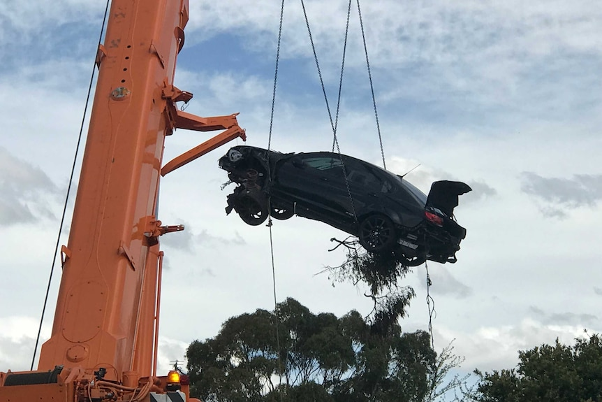 A car being lifted into the air by a crane.
