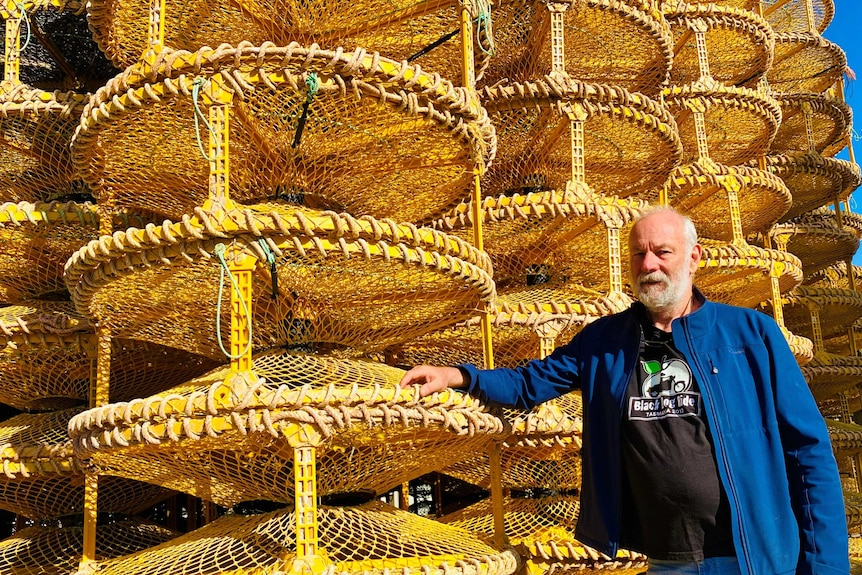 A man standing next to a stack a crab pots.