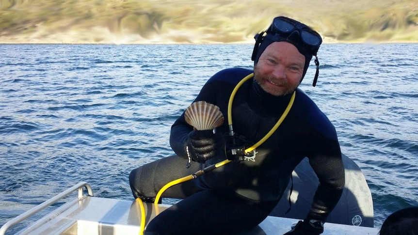 Play Audio. Photograph of a white man in a wetsuit holding a scallop shell. Duration: 13 minutes 54 seconds