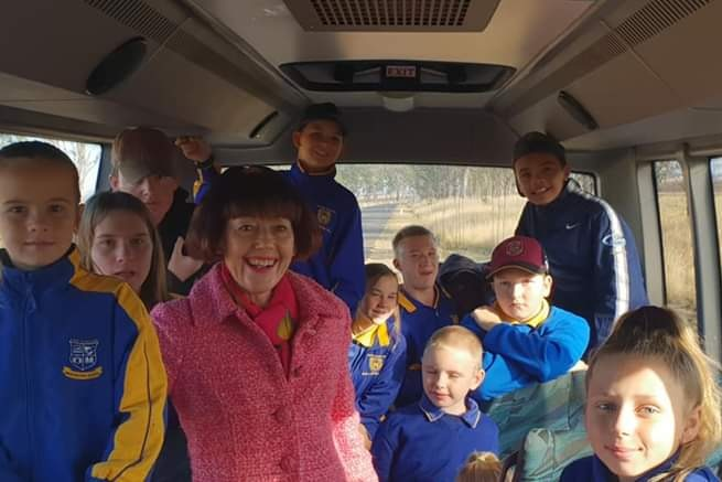 A woman in pink on a school bus with children.