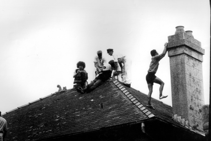 Police and protesters on the roof of a house, with the police detaining one man as another climbs a chimney.