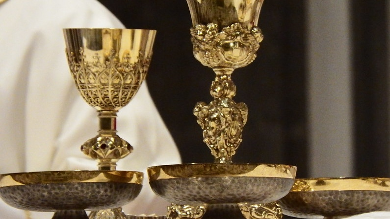 Two gold chalices and three bowls containing communion wafers.