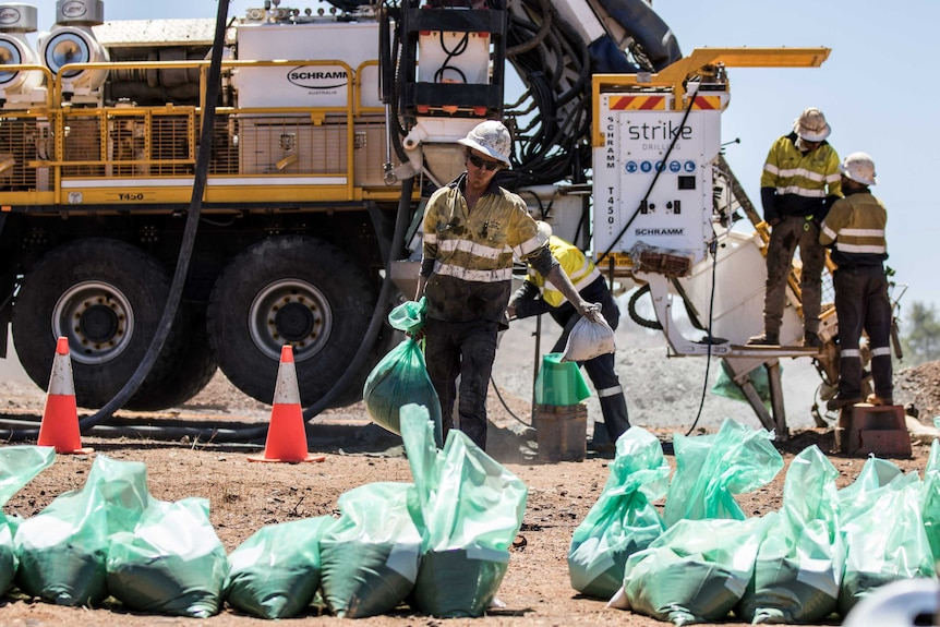 A mining worker wearing high-vis clothing carrying drilling samples.