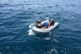 A rubber raft in the middle of a blue sea with two men on board, one carrying a man's body.