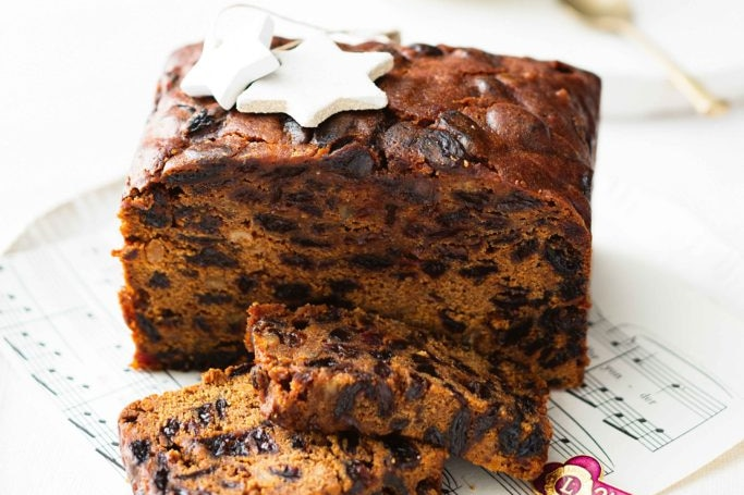 A square fruit cake with festive decorations.