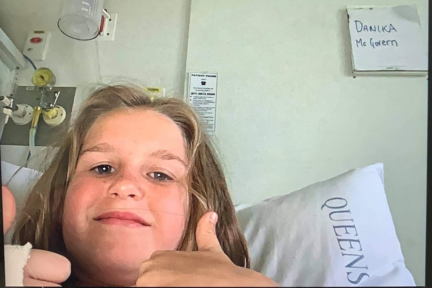 A young girl sits in a hospital bed and gives the thumbs up.
