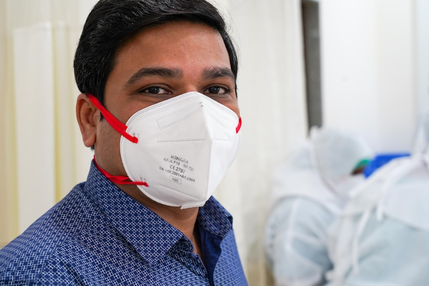 An Indian man in a blue shirt and a white face mask