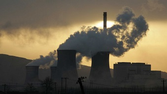 A coal-fired power plant surrounded by smog and smoke