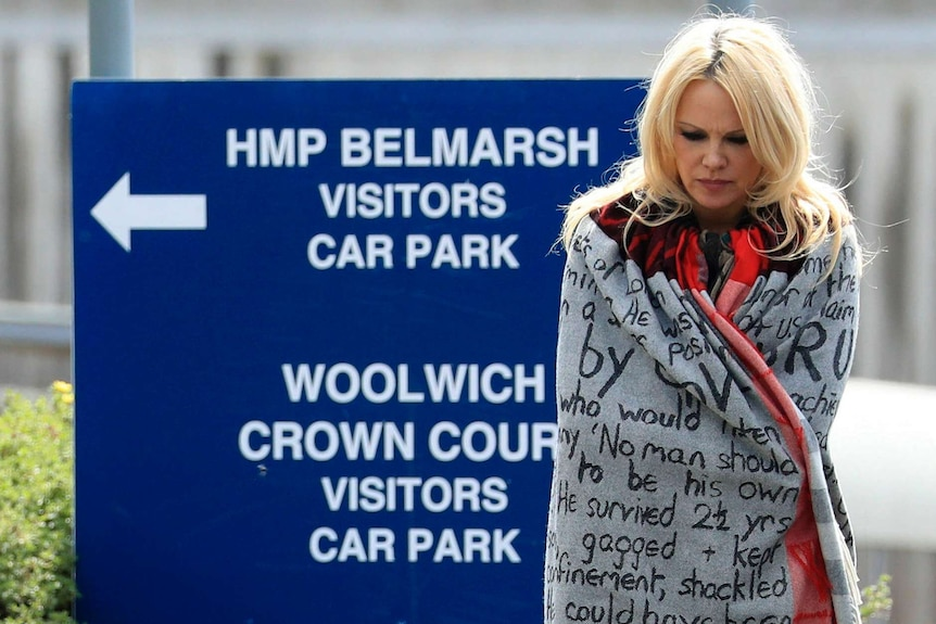 A blonde woman wrapped in a blanket with protest words written on it stands in front of a sign to a prison.