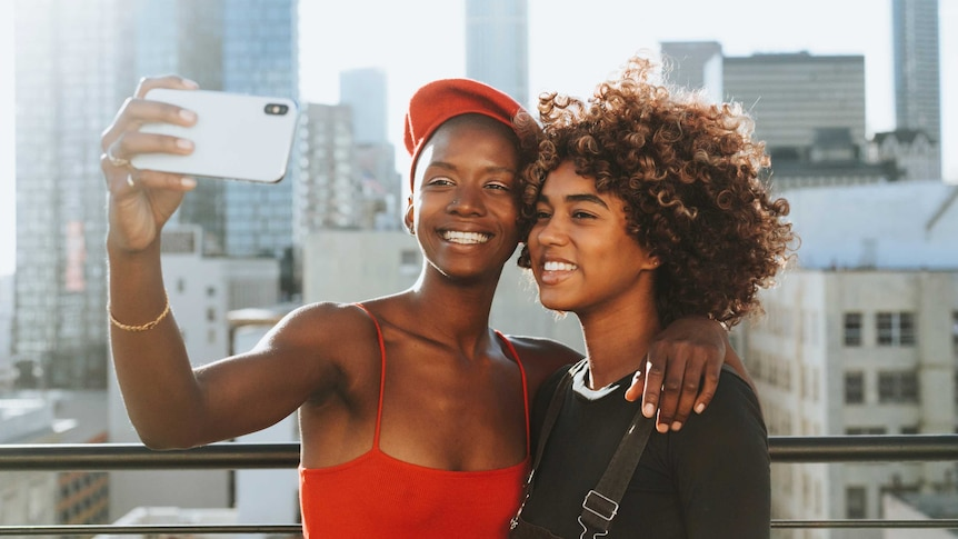 Two women smiling taking a photo on a phone together