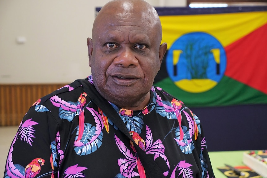 Kerry Warkill, dark skin, brown eyes, bald, wearing bright patterned t-shirt looks at the camera.