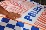 An Indigenous man's hand on the bonnet of  a police car painted with Aboriginal designs.