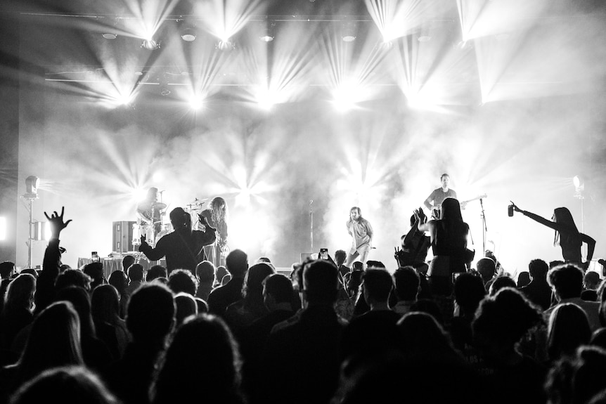 A crowd watches a band perform on a stage with bright lights behind it
