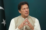 Imran Khan wearing white with his hands forming a triangle.