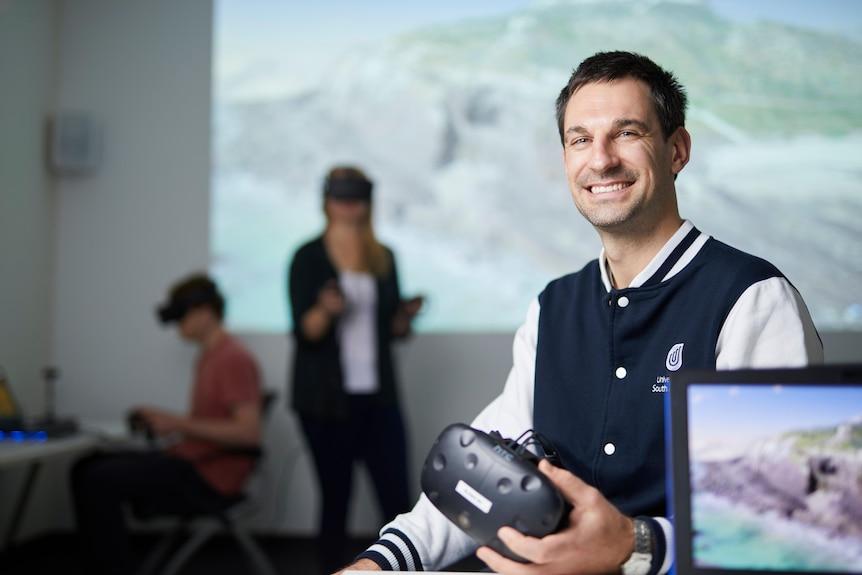 Un hombre sonriendo mientras sostiene una tecnología de realidad virtual.