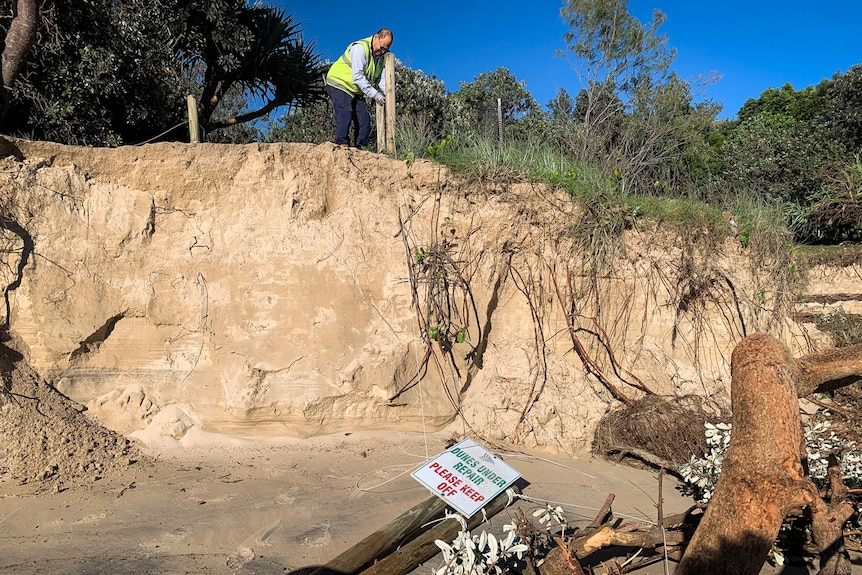 A council worker stands on top of an eroded sand dune as a sign saying 'dunes under repair' lies on the sand.